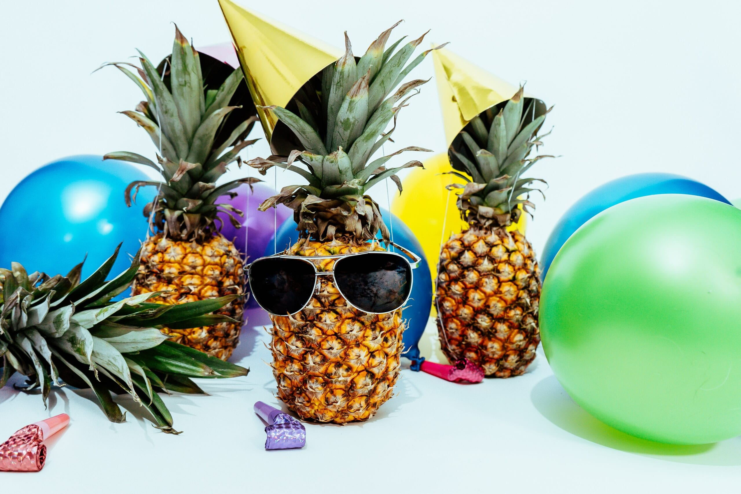 Pineapples dressed up and celebrating and having a party. The SpeakEasy Cooperative is four years old please celebrate with us