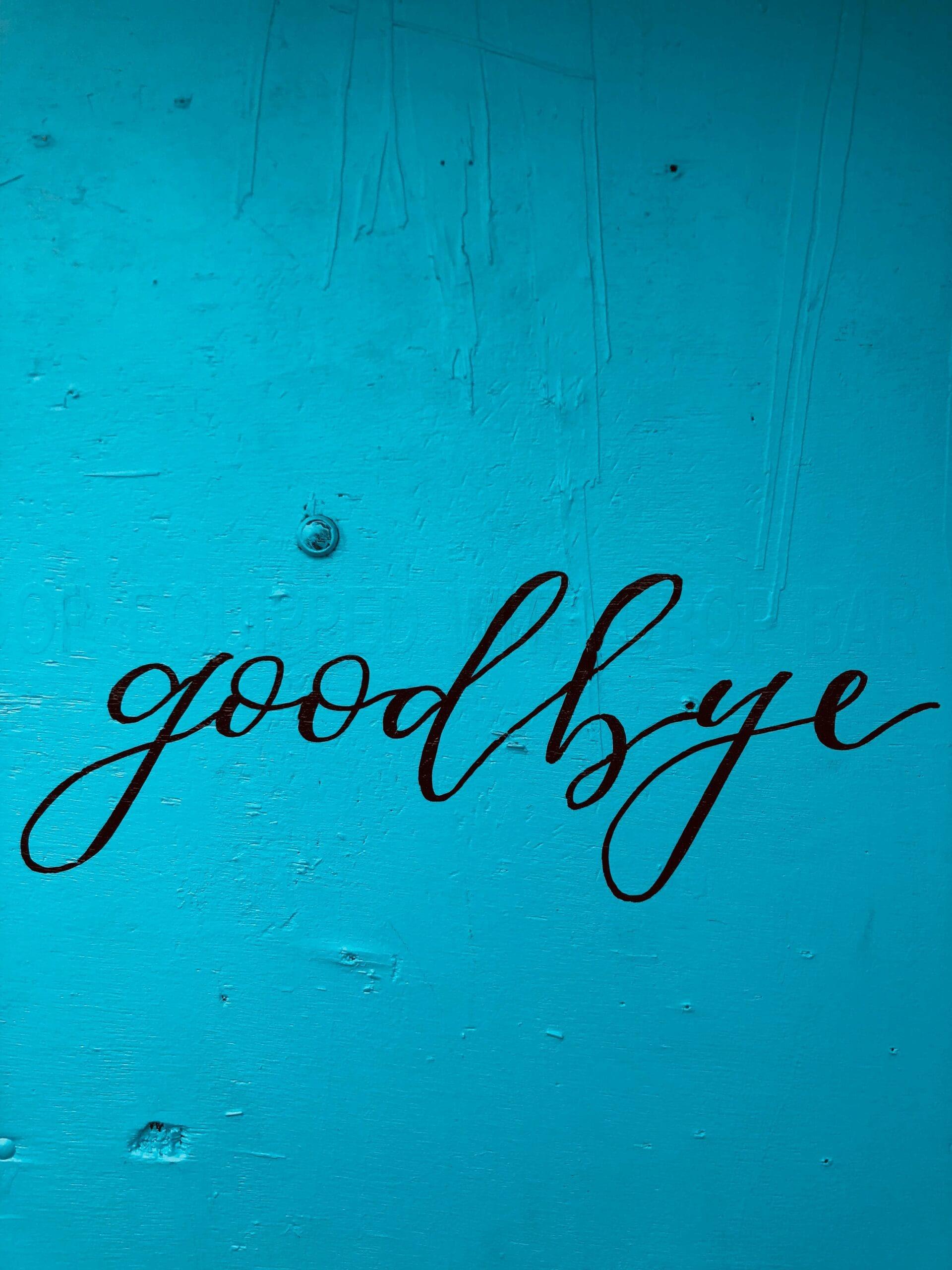"""the word """"goodbye"""" on a blue wall, inviting someone to leave because they are no longer a good fit for your studio"""